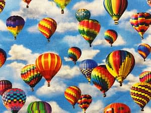Blue fabric with multicoloured and varying sized hot air balloons pattern