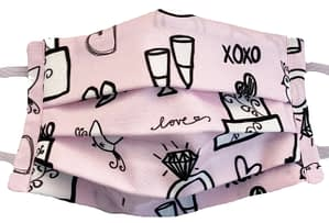 Pink fabric mask with pattern of wedding themed items like cake shoes glasses