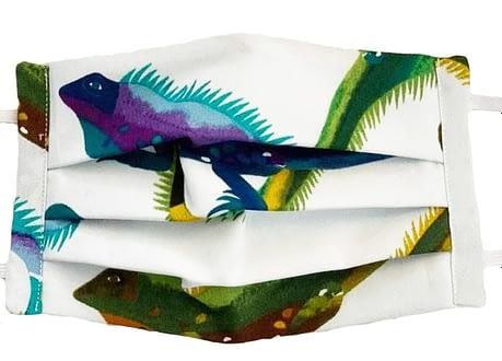 White fabric mask closeup with colourful iguanas pattern