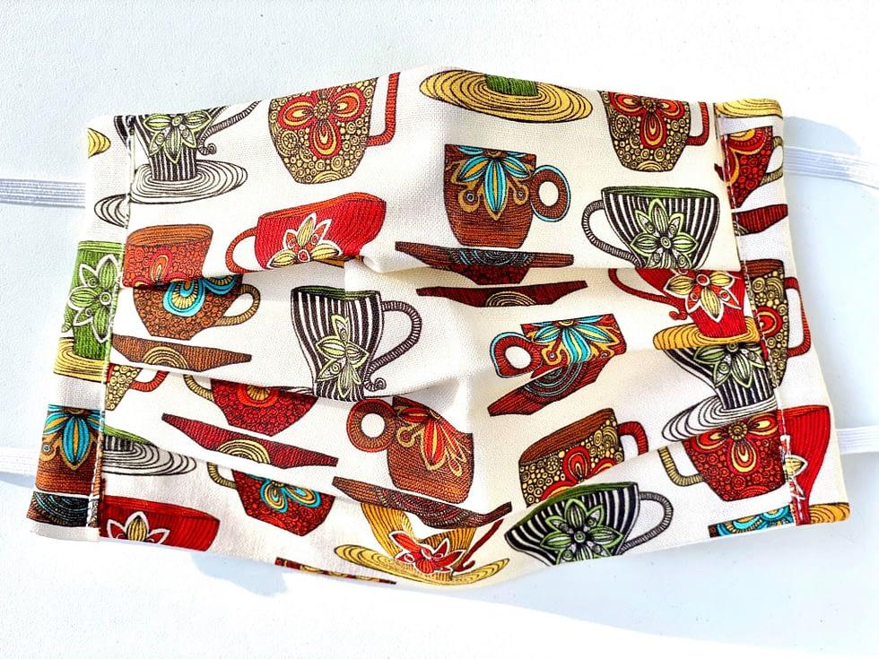 Teacups Mask Closeup | closeup cream fabric with multicoloured teacups and saucers design