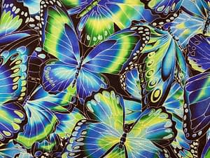 Blue green and black fabric with overlaying butterflies pattern