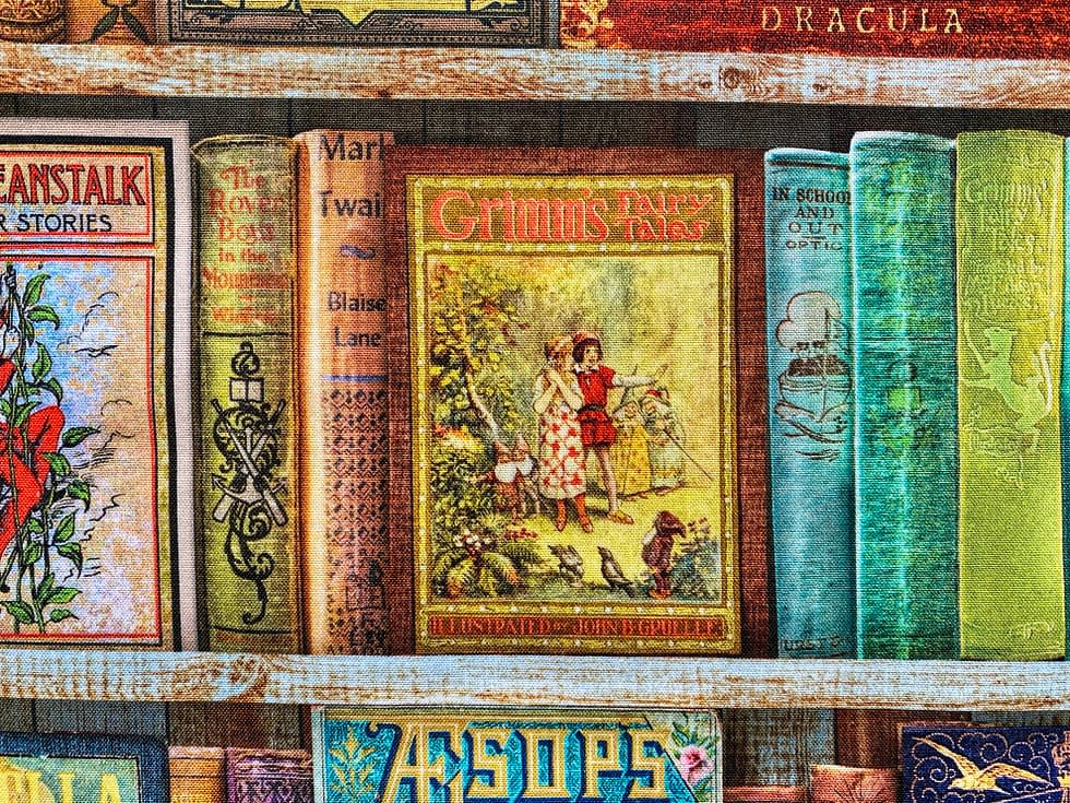 Classic Childrens' Books Fabric Closeup | Shelves of childrens' books centred on Grimm's Fairy Tales cover