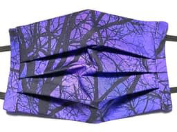 Closeup of dark purple fabric mask with pattern of leafless trees in black
