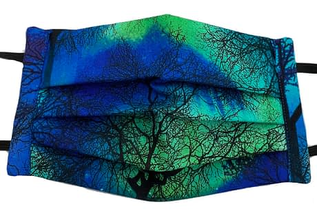 Dark blue fabric with aurora borealis pattern with silhouettes of a forest mask closeup