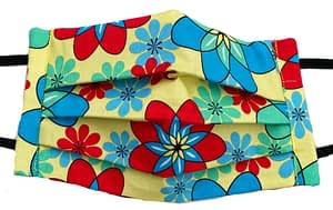 Yellow fabric with red, blue and turquoise flower shapes that resemble atomic symbols mask closeup