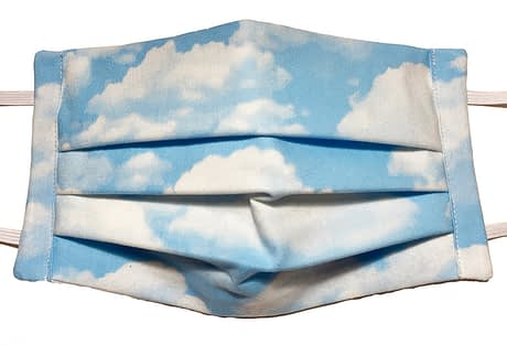 Closeup of mask with light blue fabric with fluffy white clouds