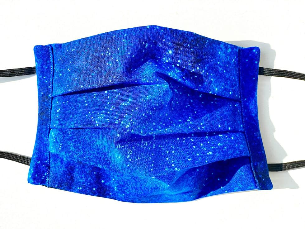 Starry Night Mask Closeup   closeup dark blue fabric with illustrated stars and lighter blues variation