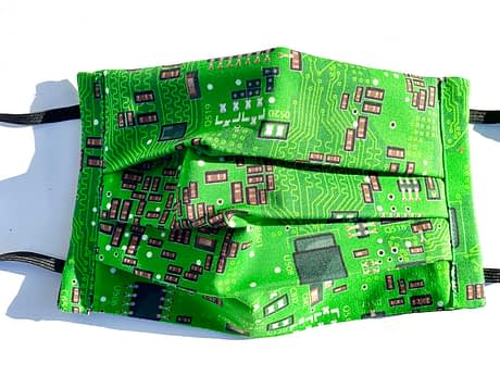 Circuit Board Mask Closeup | closeup of bright green fabric with illustrations of a circuit board in black white and grey