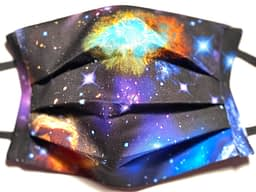 Close up of black fabric mask with pattern of galaxies, nebulae and stars