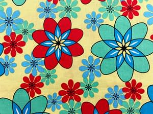 Yellow fabric with red, blue and turquoise flower shapes that resemble atomic symbols