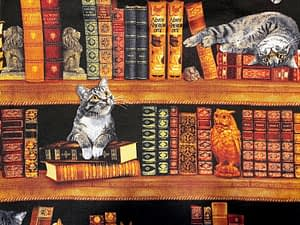 Black fabric with bookshelf and cats playing and sleeping pattern