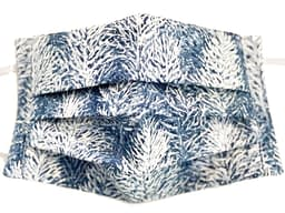 White and blue fabric mask closeup with wintry forest pattern