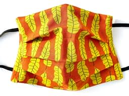 Autumn Leaves Mask Closeup |closeup of dark orange fabric with yellow long shaped leaves