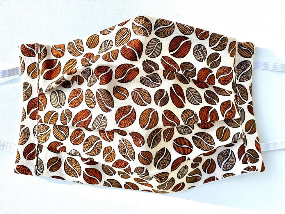 Coffee Beans Mask Closeup | closeup of cream coloured fabric mask with illustrations of coffee beans